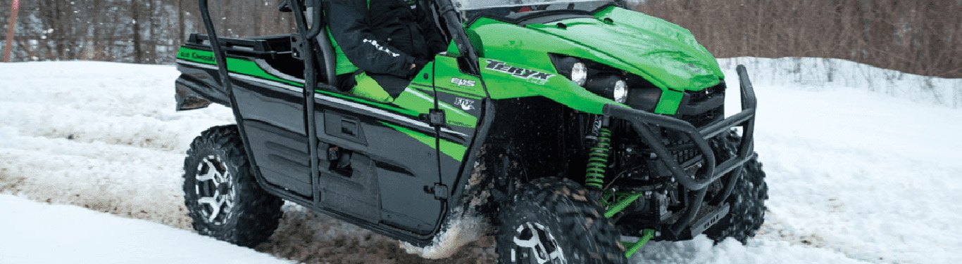 A close-up of a green ATV in the snow.
